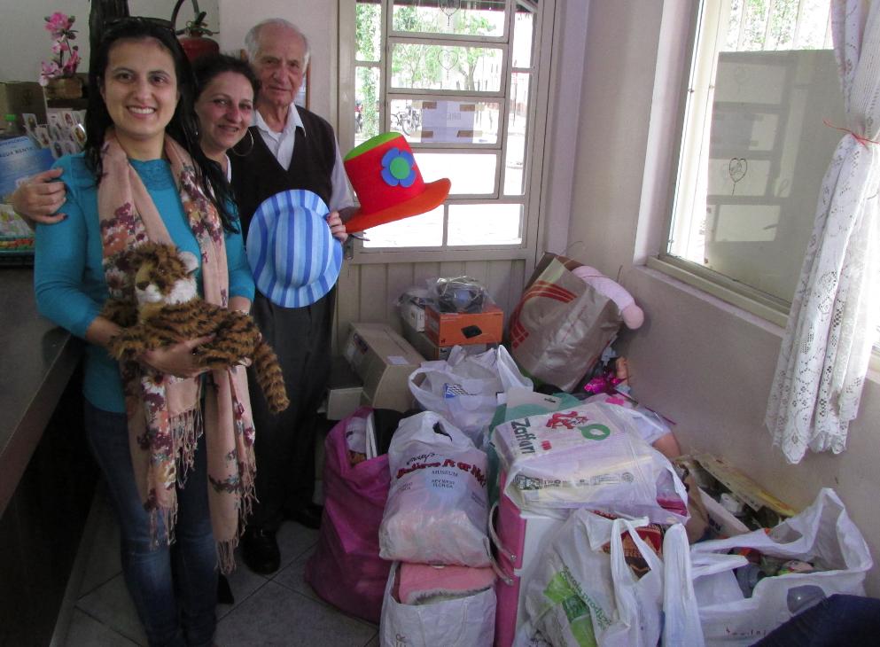 Fabiane Prusch, gerente comercial da Exotics, entrega as doações ao Irmão Vitorino e à Cássia, do Pão dos Pobres